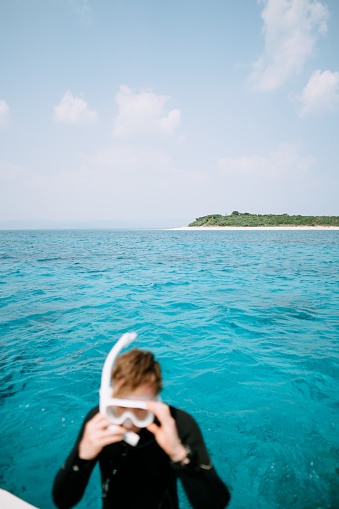 Tropical island on horizon with man putting on snorkel mask, Okinawa, Japan - gettyimageskorea