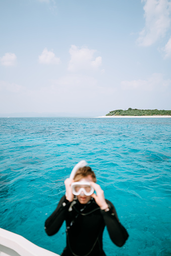 Tropical island on the horizon with man putting on snorkel mask, Okinawa, Japan - gettyimageskorea