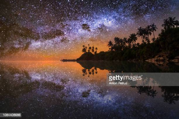 tropical island with palm trees under starry sky with milky way. romantic holidays in the tropics - 南アジア ストックフォトと画像