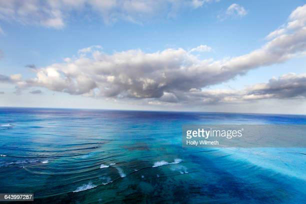 tropical ocean under cloudy blue sky - waikiki stock pictures, royalty-free photos & images