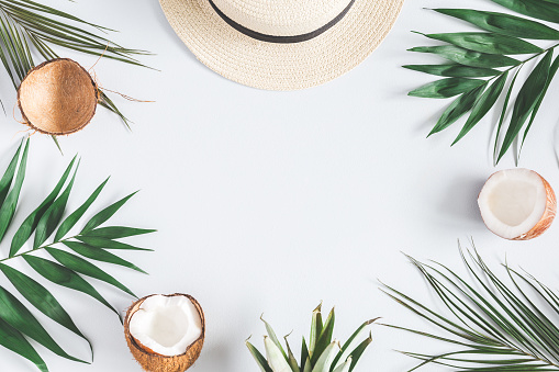 Tropical palm leaves, hat, coconut on pastel blue background 965492742