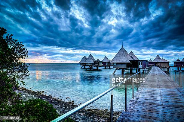 tropical paradise luxury over water resort at sunset - new caledonia stock photos and pictures