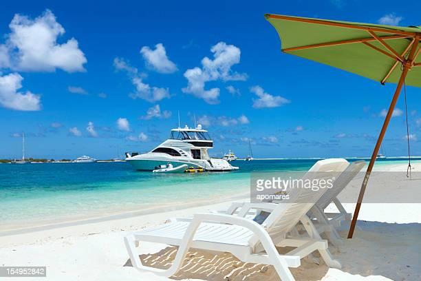 Paradis Tropical avec chaises longues, des parasols et un yacht