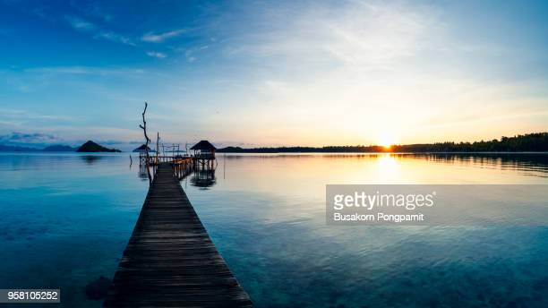 tropical seascape. the wooden bridge stretches to the sea at sunset on Koh Mak.