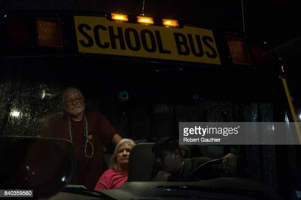 Tropical Storm Harvey evacuees arrive by bus to a shelter at BF Terry High School