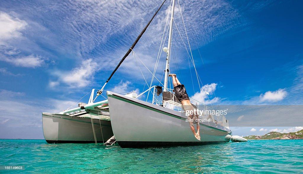 Tropical Vacation: Man Diving Off Sailboat : Stock Photo