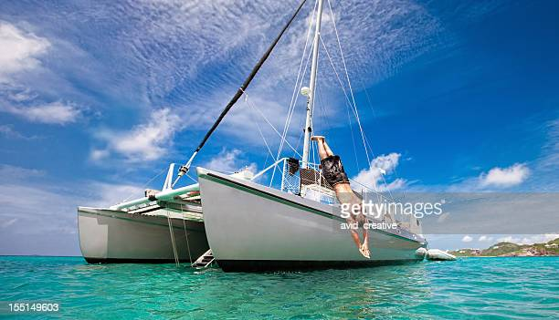 tropical vacation: man diving off sailboat - catamaran stock photos and pictures