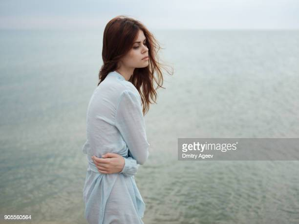 troubled caucasian woman standing near ocean - good; times bad times stock pictures, royalty-free photos & images