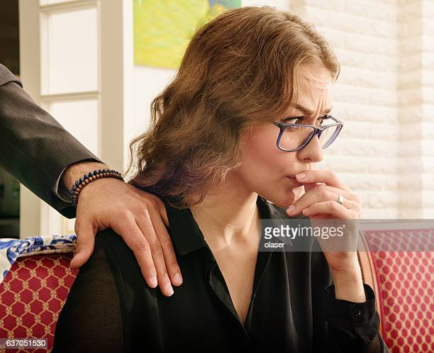 Troubled harrassed woman dislikes his hand. She wears ring.