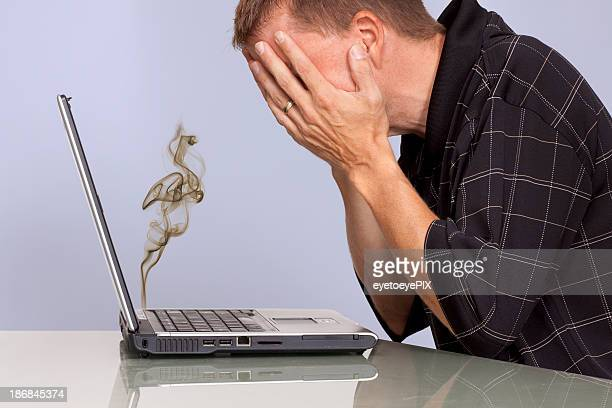 troubled man with smoking laptop computer - error message stock pictures, royalty-free photos & images