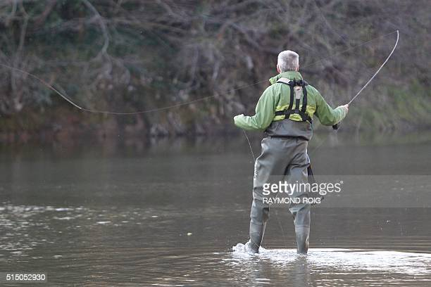 A trout fisherman holds his rod on the river Tech coming from the Pyrenees during the river fishing opening at AmélielesBains on March 12 2016 / AFP...
