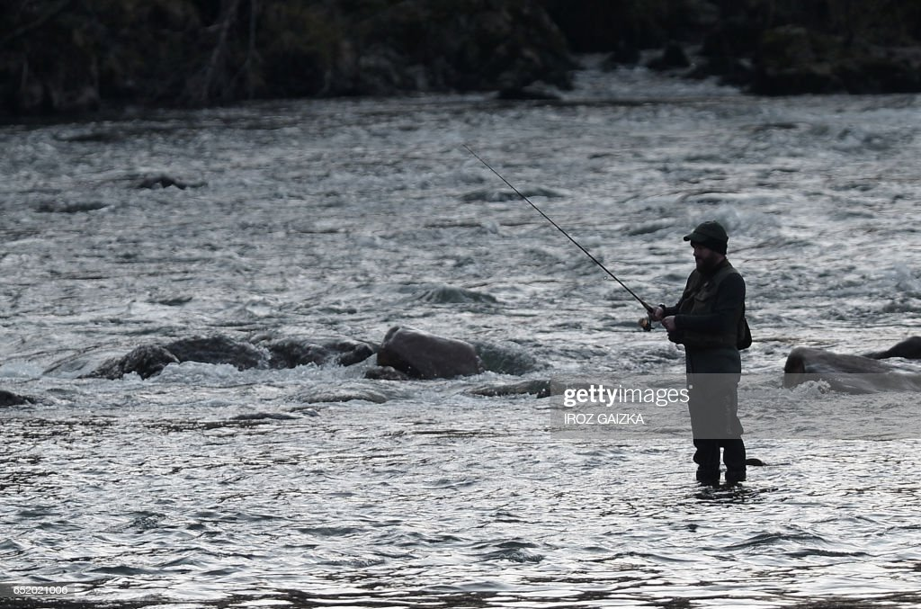 A trout fisherman waits for a catch at the start of the fishing season at the River Nive in Itxassou on March 11, 2017. /