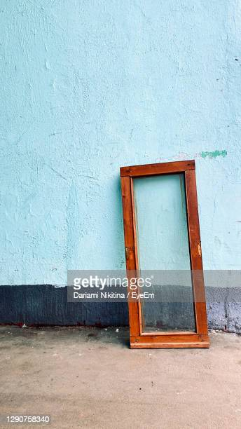 trown away window frame and a blue wall - nikitina stock pictures, royalty-free photos & images