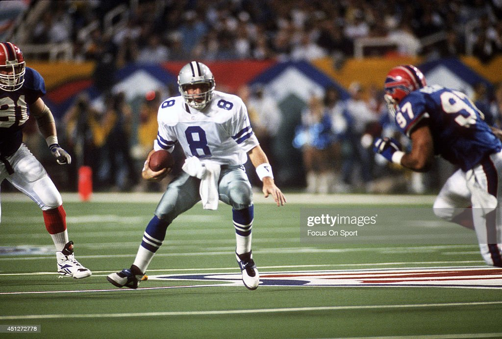 Troy Aikman #8 of the Dallas Cowboys scrambles with the ball pursued by Cornelius Bennett #97 of the Buffalo Bills during Super Bowl XXVIII on January 30, 1994 at the Georgia Dome in Atlanta, Georgia. The Cowboys won the Super Bowl 30 -13.