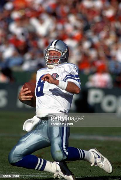 Troy Aikman of the Dallas Cowboys scrambling with the ball goes into a slide against the San Francisco 49ers during the NFL Football game November 13...