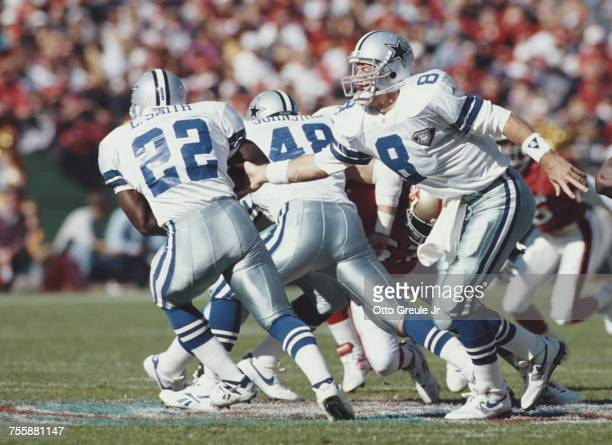 Troy Aikman Quarterback for the Dallas Cowboys hands off to running back Emmitt Smith during the National Football Conference West game against the...