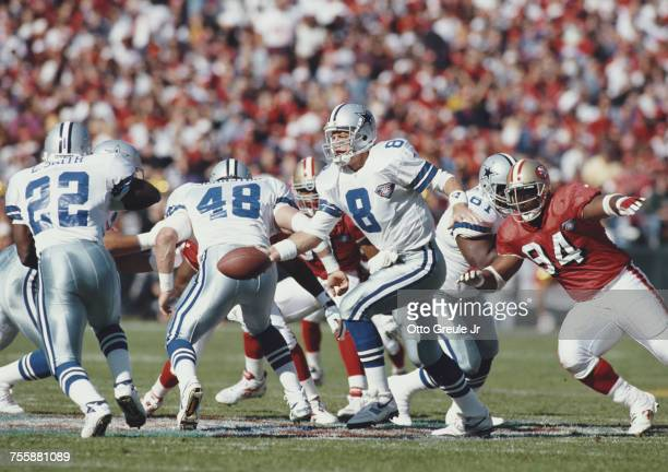 Troy Aikman Quarterback for the Dallas Cowboys is hands off to running back Emmitt Smith during the National Football Conference West game against...