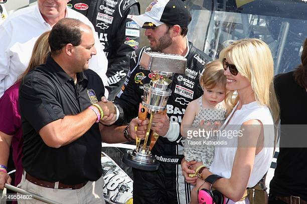 "Troy Alabama Fire Lieutenant Curtiss Shaver winner of Crown Royal's ""Your Hero's Name Here"" program presents the trophy to Jimmie Johnson driver of..."