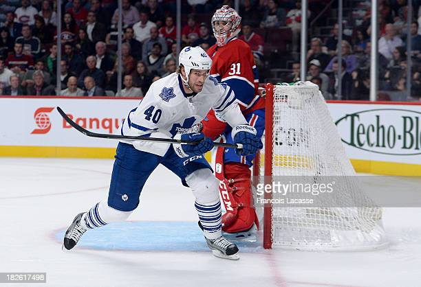 Troy Bodie of the Toronto Maple Leafs chases the puck while Carey Price of the Montreal Canadiens watches the action during the NHL game on October...