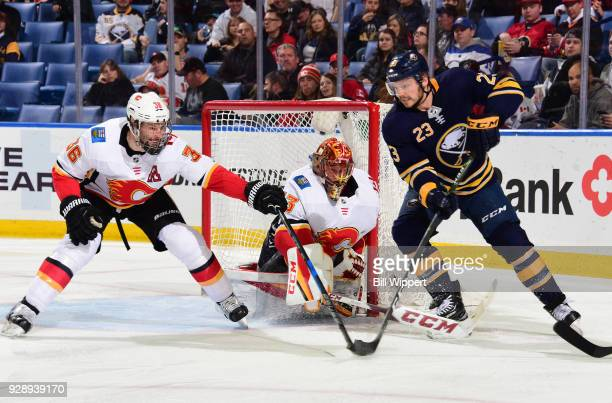 Troy Brouwer and David Rittich of the Calgary Flames defend against Sam Reinhart of the Buffalo Sabres during the second period of an NHL game on...