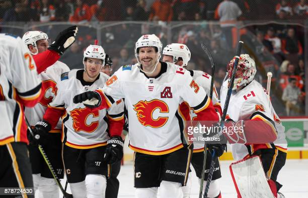 Troy Brouwer and Travis Hamonic of the Calgary Flames celebrate with teammates after defeating the Philadelphia Flyers 54 in overtime on November 18...