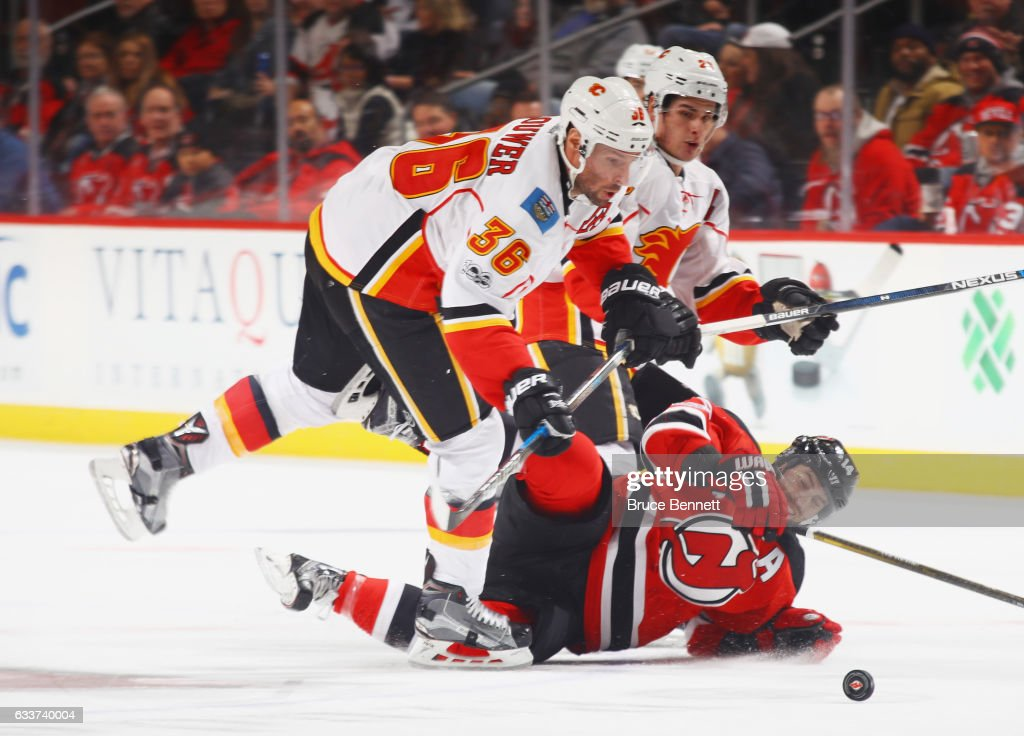 Troy Brouwer #36 of the Calgary Flames checks Adam Henrique #14 of the New Jersey Devils during the third period at the Prudential Center on February 3, 2017 in Newark, New Jersey. The Flames defeated the Devils 4-3 in overtime.