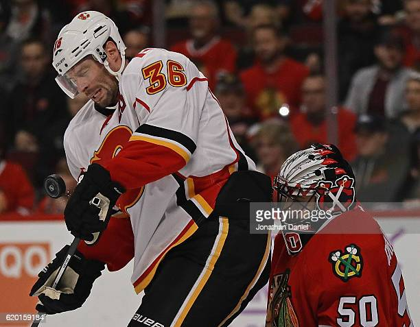 Troy Brouwer of the Calgary Flames is hit by the puck as he screens Corey Crawford of the Chicago Blackhawks at the United Center on November 1 2016...