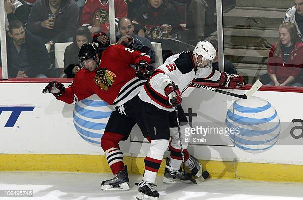 Troy Brouwer of the Chicago Blackhawks and Colin White of the New Jersey Devils get tangled by the boards on November 03 2010 at the United Center in...