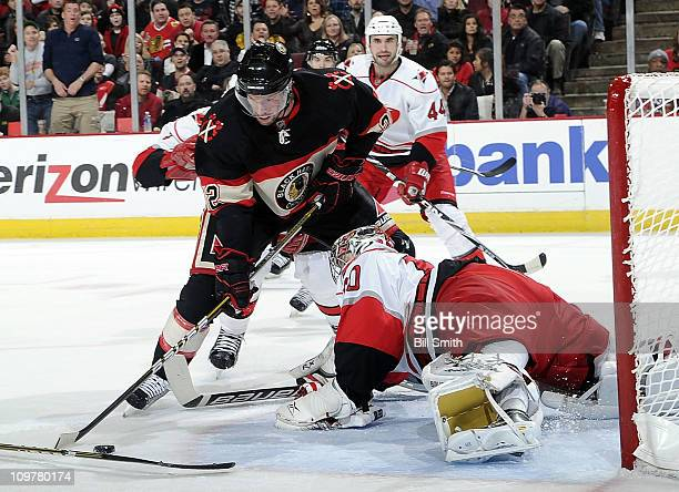 Troy Brouwer of the Chicago Blackhawks attempts to get the puck past goalie Justin Peters of the Carolina Hurricanes, as Jay Harrison of the...