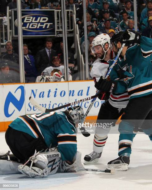 Troy Brouwer of the Chicago Blackhawks battles for the puck with Dan Boyle and Evgeni Nabokov of the San Jose Sharks in Game One of the Western...