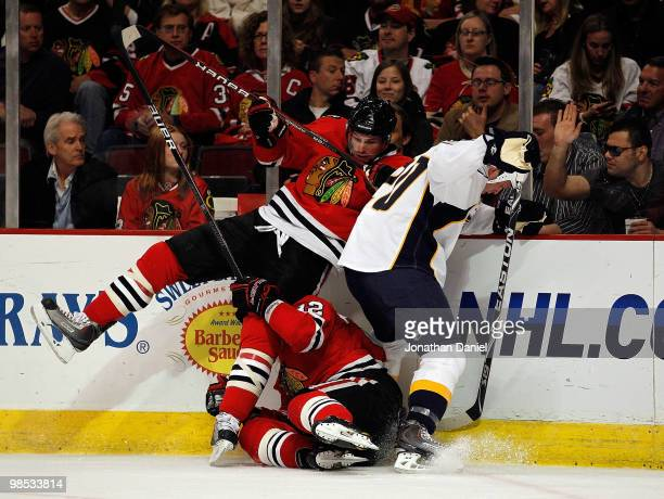 Troy Brouwer of the Chicago Blackhawks falls over teammate Kris Versteeg as they battle for the puck with Ryan Suter of the Nashville Predators in...