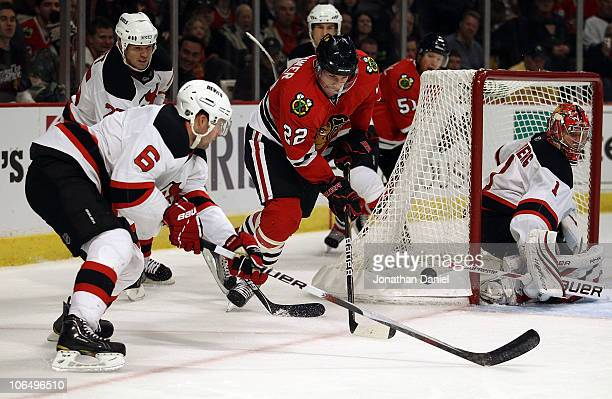 Troy Brouwer of the Chicago Blackhawks tries to control the puck near the goal as Andy Greene of the New Jersey Devils defends at the United Center...