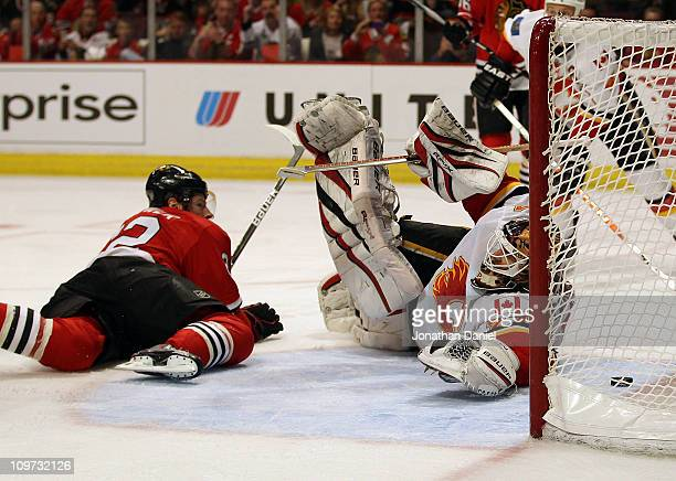 Troy Brouwer of the Chicago Blackhawks watches from the ice as the puck slips past Miikka Kiprusoff of the Calgary Flames on a goal by Jonathan Toews...