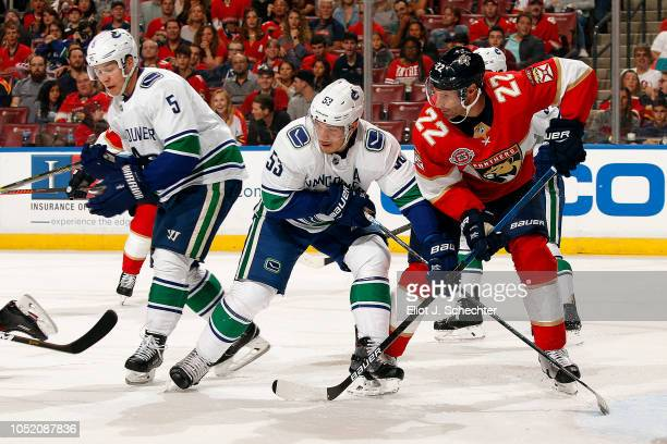 Troy Brouwer of the Florida Panthers crosses sticks with Bo Horvat of the Vancouver Canucks at the BBT Center on October 13 2018 in Sunrise Florida