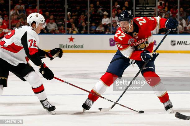 Troy Brouwer of the Florida Panthers crosses sticks with Thomas Chabot of the Ottawa Senators at the BBT Center on November 11 2018 in Sunrise Florida