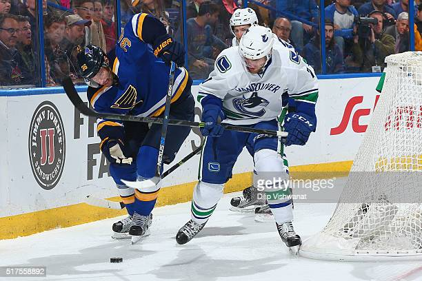 Troy Brouwer of the St Louis Blues and Linden Vey of the Vancouver Canucks fight for control of the puck at the Scottrade Center on March 25 2016 in...