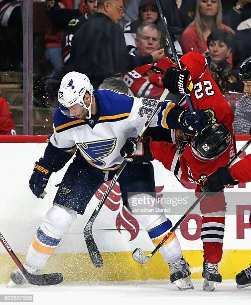Troy Brouwer of the St Louis Blues and Marcus Kruger of the Chicago Blackhawks battle along the boards in Game Four of the Western Conference First...