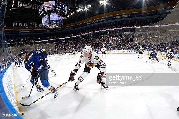 Troy Brouwer of the St Louis Blues and Viktor Svedberg of the Chicago Blackhawks battle for the puck in Game One of the Western Conference First...
