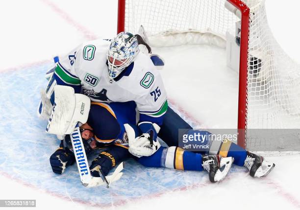 Troy Brouwer of the St. Louis Blues ends up under Jacob Markstrom of the Vancouver Canucks during the second period in Game One of the Western...
