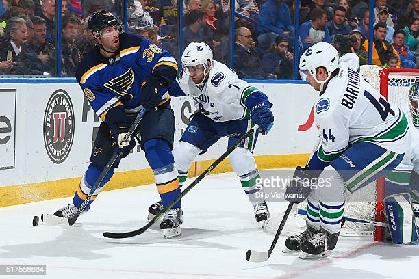 Troy Brouwer of the St Louis Blues passes the puck against Linden Vey of the Vancouver Canucks at the Scottrade Center on March 25 2016 in St Louis...