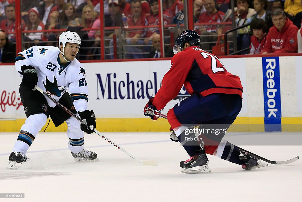Troy Brouwer #20 of the Washington Capitals skates with the puck against Scott Hannan #27 of the San Jose Sharks during the second period at Verizon Center on October 14, 2014 in Washington, DC.