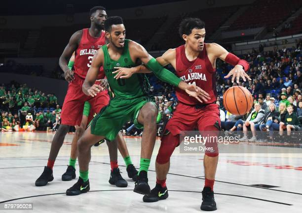 Troy Brown of the Oregon Ducks and Trae Young of the Oklahoma Sooners battle for a loose ball as Khadeem Lattin of the Oklahoma Sooners looks on...