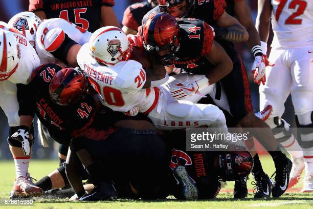 Troy Cassidy and Tariq Thompson of the San Diego State Aztecs tackle Daryl Chestnut of the New Mexico Lobos during the first half of a game at...