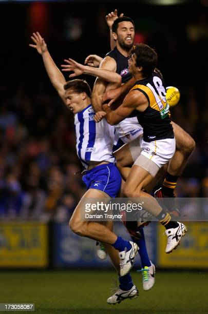 Troy Chaplin and Alex Rance of the Tigers spoils Drew Petrie of the Kangaroos during the round 15 AFL match between the North Melbourne Kangaroos and...