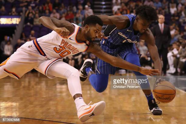Troy Daniels of the Phoenix Suns and Jonathan Isaac of the Orlando Magic dive for a loose ball during the first half of the NBA game at Talking Stick...