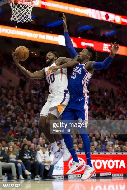 Troy Daniels of the Phoenix Suns attempts a lay up against Robert Covington of the Philadelphia 76ers at the Wells Fargo Center on December 4 2017 in...