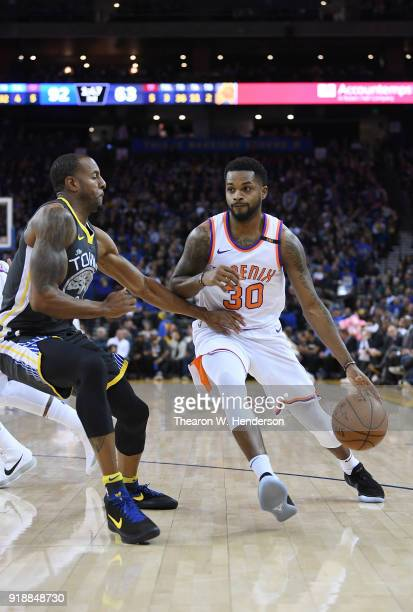Troy Daniels of the Phoenix Suns dribbles the ball while guarded by Andre Iguodala of the Golden State Warriors during an NBA basketball game at...
