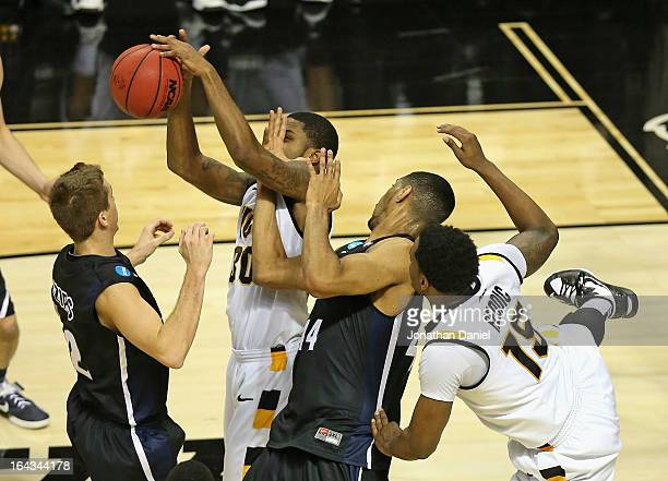 Troy Daniels of the VCU Rams tries to rebound as he is hit by Zeke Marshall of the Akron Zips as Brian Walsh defends and Juvonte Reddic battles...