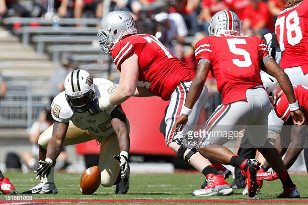 Troy Davis of the Central Florida Knights covers up a loose ball before Jack Mewhort of the Ohio State Buckeyes is able to fall on it during the...