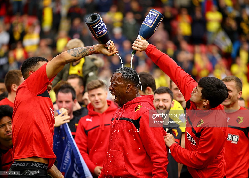 Troy Deeney and Fernando Forestieri pour chamagne on Lloyd Doyley as they celebrate promotion to the premier league during the Sky Bet Championship match between Watford and Sheffield Wednesday at Vicarage Road on May 2, 2015 in Watford, England.